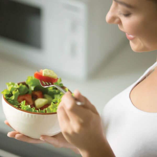 Woman enjoying a healthy bowl of veggies